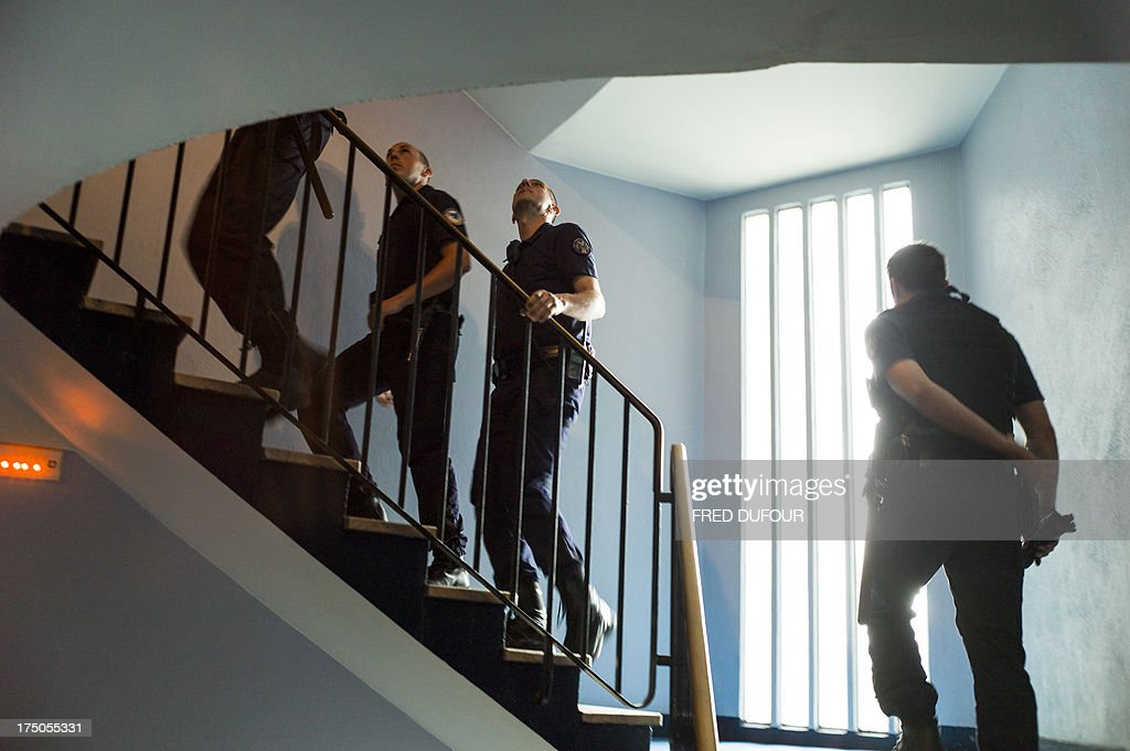 Policemen patrol in the stairs of a building in a priority security zone (ZSP) in Saint-Denis, a Paris suburb on July 30, 2013. AFP PHOTO / FRED DUFOUR