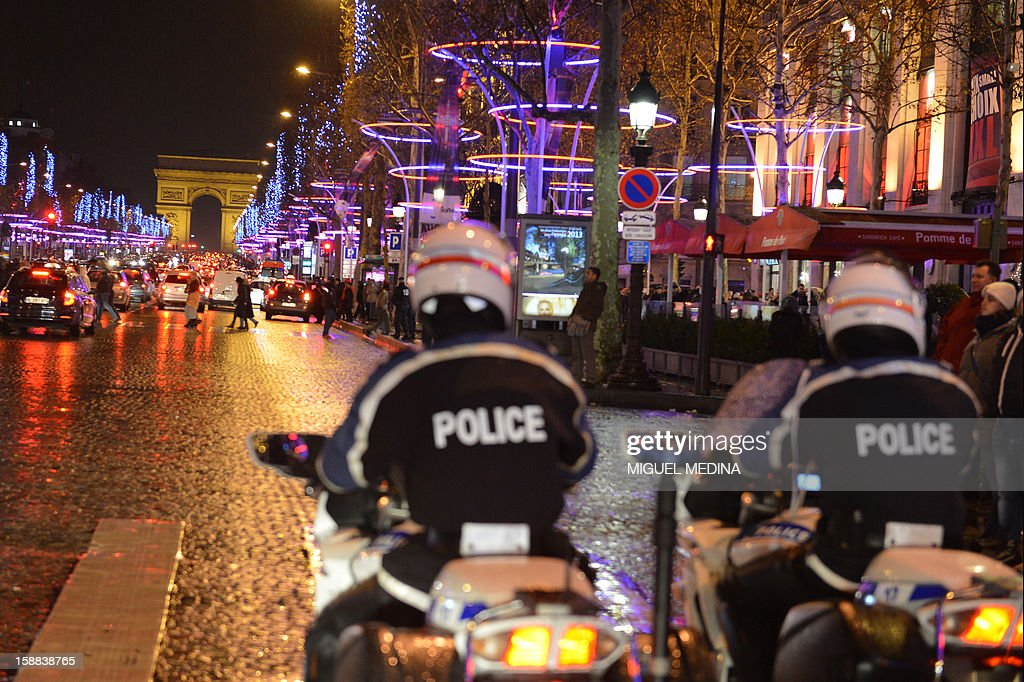 Policemen patrol late on December 31, 2012 on the Champs-Elysees avenue in Paris, where revellers arrive one hour ahead of New year celebrations.