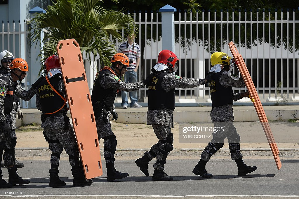 Policemen protect themselves with stretchers as anti-government demonstrators gather at the security perimeter two kilometers (1.2 miles) from the Castelao stadium in Fortaleza where Spain and Italy are to clash in their FIFA Confederations Cup Brazil 2013 semifinal football match, on June 27, 2013. Earlier riot and mounted police set up roadblocks on access roads leading to the stadium as several thousand young demonstrators peacefully rallied outside Ceara State University in Fortaleza hours before the match. Nationwide anti-government protests in Brazil initially focused on a hike in transport fares before mushrooming to encompass a variety of gripes including corruption and the lack of investment in health and education as well as to denounce the high costs of hosting the Confederations Cup and next year's World Cup.
