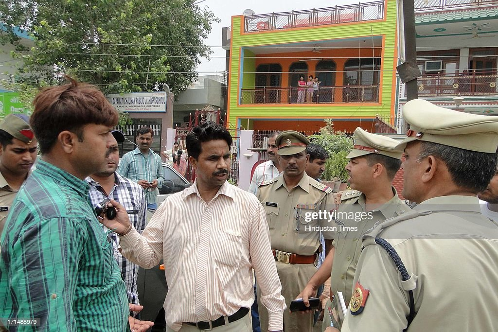 Policemen questing the onlookers after businessman was robbed of Rs 23.5 lakh at gun point by two bike-borne armed assailants in front of Oriental Bank of Commerce branch in Sahibabad area on June 25, 2013 in Ghaziabad, India.