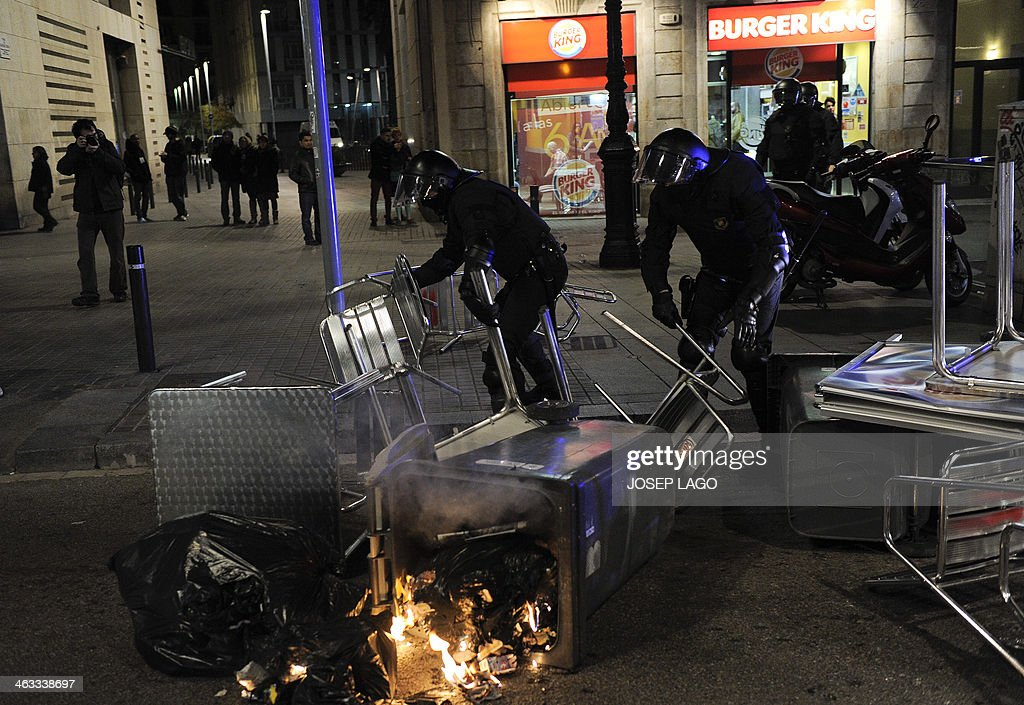 Policemen remove chairs and tables as demonstrators clash during a demonstration in Barcelona on January 17, 2014 in support of locals from the city of Burgos protesting against planned construction works to revamp Vitoria street, the city's main thorough-fare. After a week of protest, Burgos' mayor announced today the abandonment of the project. The nightly protests began on January 10 and have spread from Burgos, to Madrid and to the town of Valladolid.