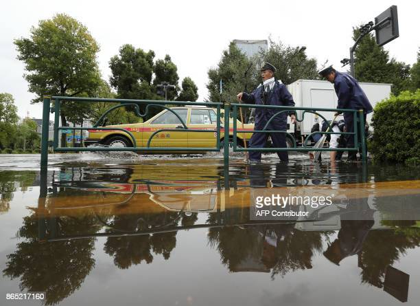 Policemen remove leaves from a drain on a flooded road in Tokyo on October 23 2017 A powerful typhoon left two dead two missing and dozens injured in...