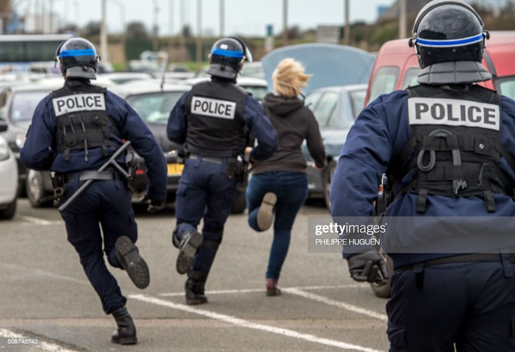Policemen run after a supporter of the Pegida movement (Patriotic Europeans Against the Islamisation of the Occident) during a demonstration in Calais, northern France on February 6, 2016. Anti-migrant protesters in the French port city of Calais clashed with police as they defied a ban and rallied in support of a Europe-wide initiative by the Islamophobic Pegida movement. / AFP / PHILIPPE HUGUEN