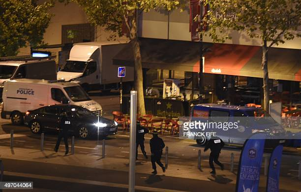 Policemen run outside the Stade de France in SaintDenis north of Paris after the friendly football match France vs Germany on November 13 2015...