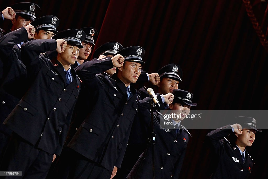 Policemen salute at the admission ceremony of Communist Party of China during a gala show to celebrate the 90th anniversary of the founding of the Communist Party of China (CPC) in the Great Hall of the People on June 28, 2011 in Beijing, China. This year's celebrations will mark the 90th anniversary of the founding of the CPC.