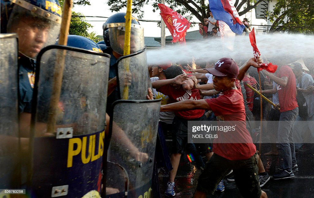 Policemen scuffle with activists during the Labor Day protest in front of the US embassy in Manila on May 1, 2016. Thousands of workers and activists marched on Philippine streets marking May Day to protest the government's migrant labour policy and demand higher wages amid rising prices for basic commodities. / AFP / NOEL