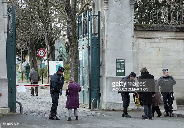 Policemen search at the entrance of the Pere Lachaise cemetery before the funeral ceremony of Charlie Hebdo's French cartoonist Honore and...