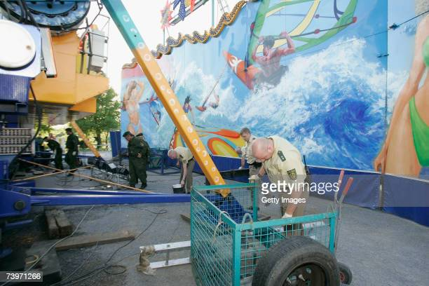 Policemen search behind a fun fair ride following the shooting of two police officers at the Theresienwiese on April 25 2007 in Heilbronn Germany...