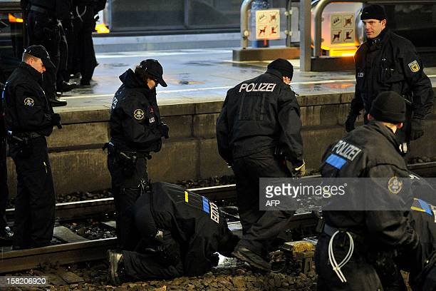 Policemen secure evidences on the tracks at the railway station in Bonn western Germany on December 10 where a bag containing a 'potentially...