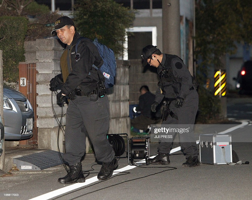 Policemen set up a cordon near a bank where a man was holding hostages in Toyokawa city in Aichi prefecture, central Japan on November 22, 2012. A knifeman was holding hostages at a Japanese bank on November 22, police said, with local media reporting he was demanding Prime Minister Yoshihiko Noda's cabinet resign.