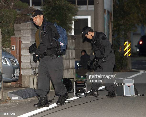 Policemen set up a cordon near a bank where a man was holding hostages in Toyokawa city in Aichi prefecture central Japan on November 22 2012 A...