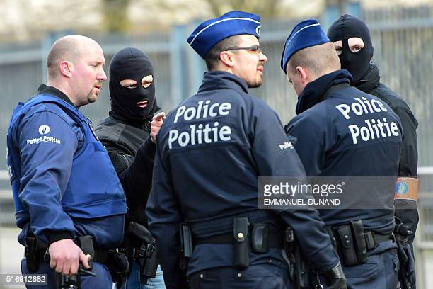 Policemen speak at a security perimeter near Maalbeek Maelbeek metro station on March 22 2016 in Brussels after a blast at this station near the EU...