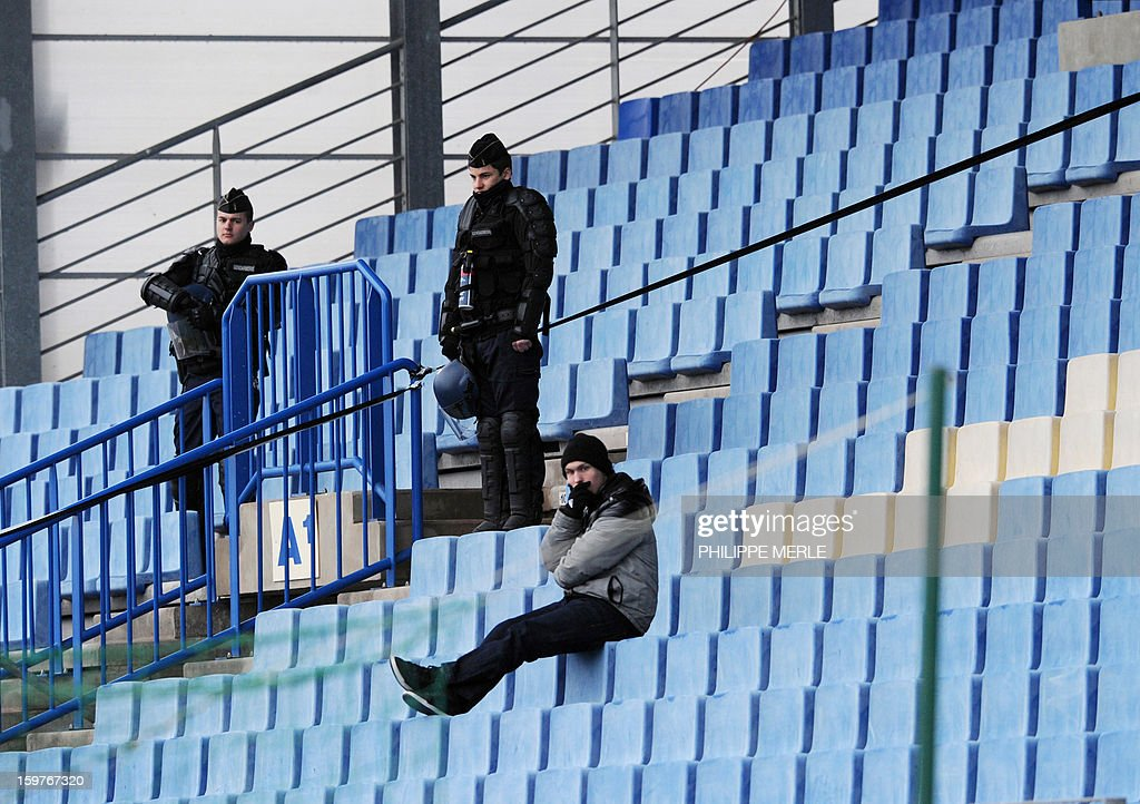 Policemen stand alongside a lone supporter watching the French L1 football match between Bastia and Rennes, on January 20, 2013, at the Jean Laville stadium in Gueugnon. The match was held in Gueugnon after the Bastia stadium was forbidden to host the three upcoming football matches involving the Bastia team. The measure was taken to punish the Bastia team and its fans for several incidents and sporadic violence which disrupted previous matches.