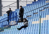Policemen stand alongside a lone supporter watching the French L1 football match between Bastia and Rennes on January 20 at the Jean Laville stadium...