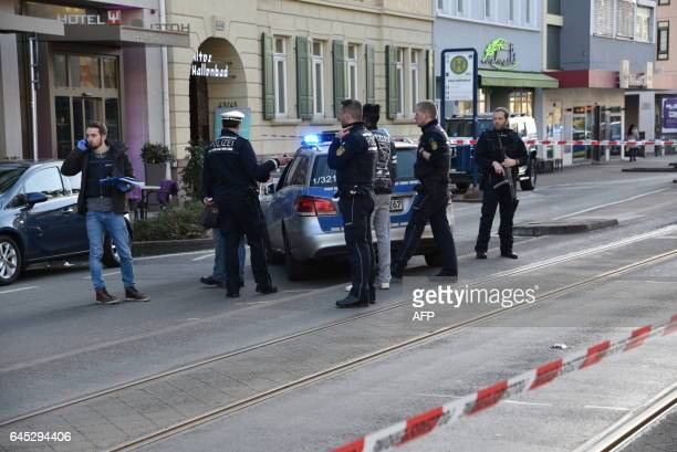 Policemen stand around a car in front of a business building in Heidelberg western Germany where a man ploughed into pedestrians on February 25 2017...