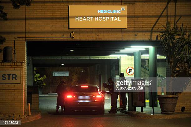 Policemen stand as a car arrives at the entrance of the MediClinic Heart Hospital on June 23 2013 in Pretoria where former South African President...