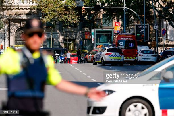 TOPSHOT A policemen stand as he blocks the street to a cordoned off area after a van ploughed into the crowd injuring several persons on the Rambla...