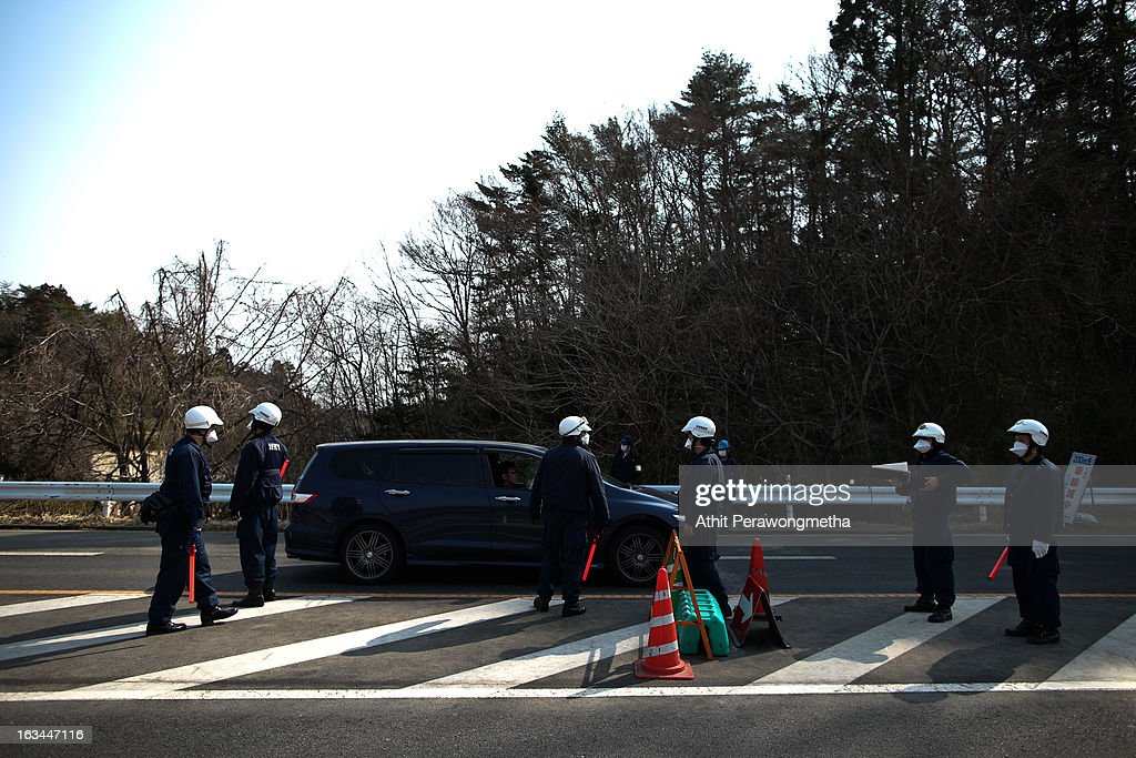 Policemen stand at a checkpoint in Namie, Fukushima Prefecture, prior to the second anniversary commemoration of the tsunami and earthquake on March 10, 2013 in Namie, Japan. Japan on March 11 will commemorate the second anniversary of the magnitude 9.0 earthquake and following tsunami, that claimed more than 18,000 lives.