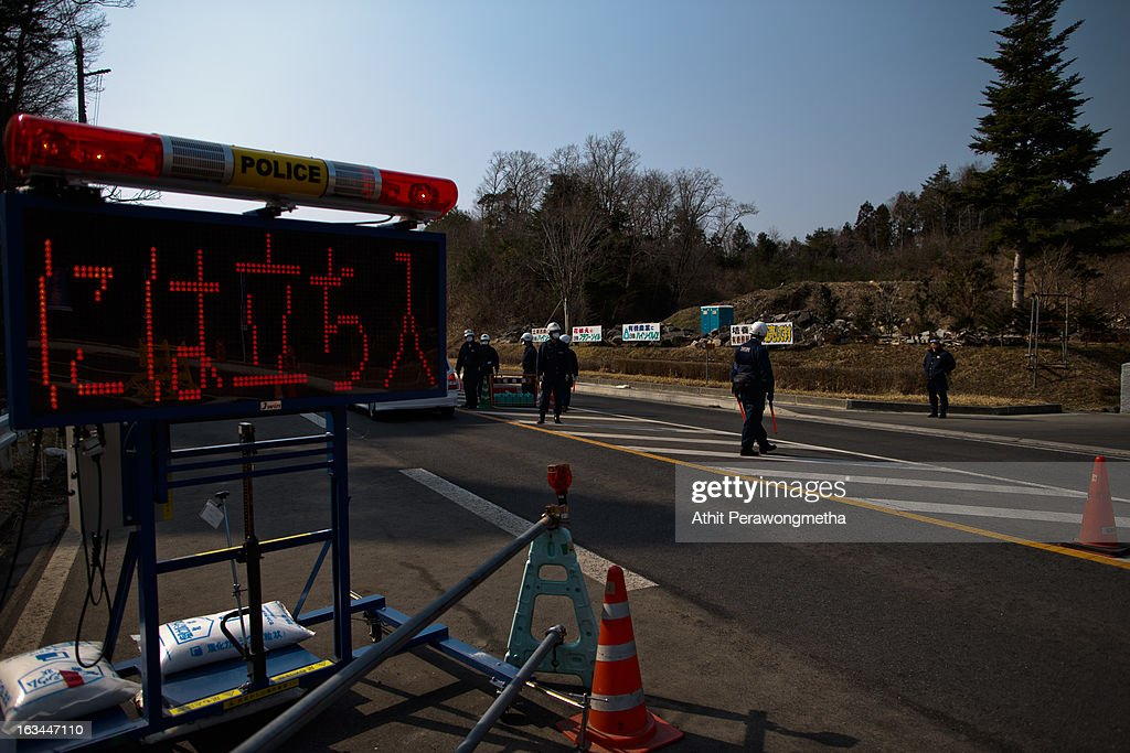 Policemen stand at checkpoint in Namie, Fukushima Prefecture, prior to the second anniversary commemoration of the tsunami and earthquake on March 10, 2013 in Namie, Japan. Japan on March 11 will commemorate the second anniversary of the magnitude 9.0 earthquake and following tsunami, that claimed more than 18,000 lives.
