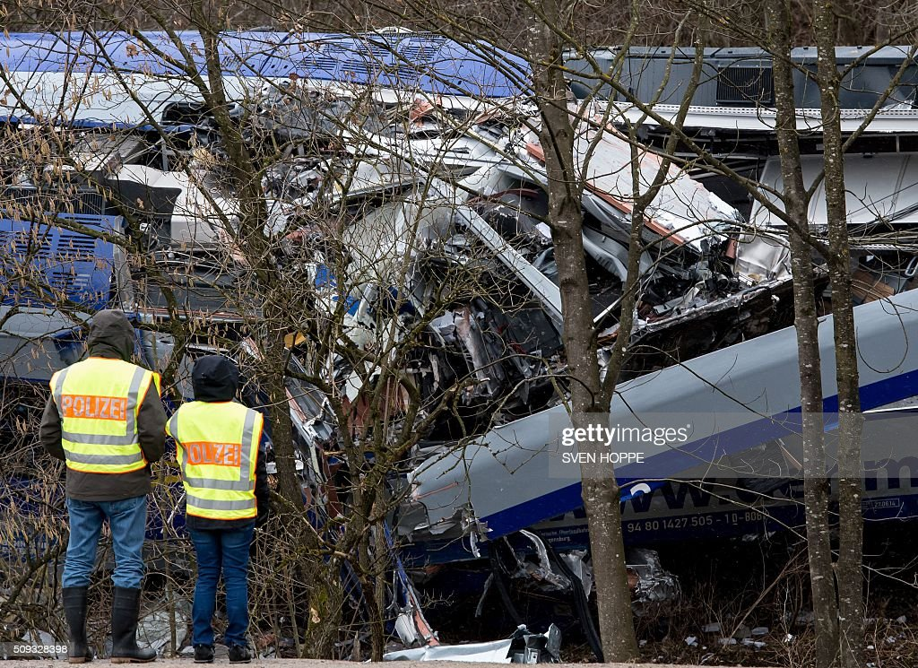 Policemen stand at the site of a train accident near Bad Aibling, southern Germany, on February 10, 2016. Two Meridian commuter trains operated by Transdev on February 9, 2016 collided head-on near Bad Aibling, around 60 kilometres (40 miles) southeast of Munich, killing at least ten people and injuring around 100, police said. / AFP / dpa / Sven Hoppe / Germany OUT