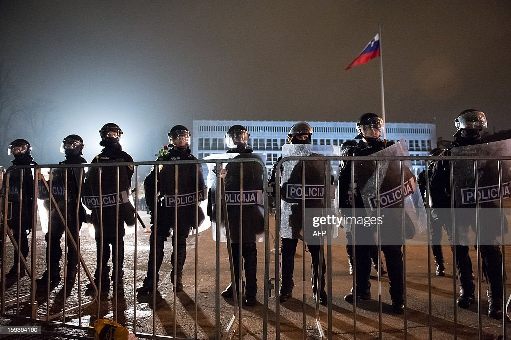 Policemen stand behind barricades set in front of the Parliament during a demonstration against political corruption and the Prime Minister in Ljubljana, on January 11, 2013. Several thousand people in Slovenia's capital today joined in one of the biggest anti-government rallies in recent months, demanding the resignation of Prime Minister Janez Jansa, who has been accused of corruption. State radio estimated over 10,000 people took part in the protest called by civil groups under the slogan 'For the government's resignation and the renewal of Slovenia.' Police put the figure closer to 8,000. AFP PHOTO / Jure Makovec