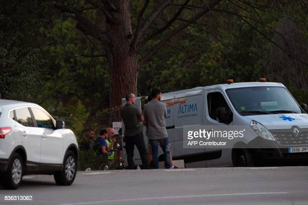 Policemen stand behind the van of the funeral services carrying the body of Moroccan suspect Younes Abouyaaqoub on the site where he was shot on...