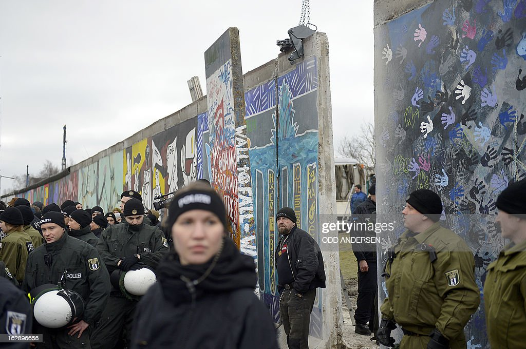 Policemen stand by a section of the East Side Gallery, a 1,3 km long remainder of the Berlin Wall, being removed by a crane near the city's east railway station in Berlin on March 1, 2013. Some 25 meters of this section of the wall that mostly came down 23 years ago and marked the end of the cold war are taken away to make way for a new housing development on river Spree, a project called Living Levels. As news of this spread activists and artists that had decorated this remaining part of the cold war relic known as the east side gallery came to protest.