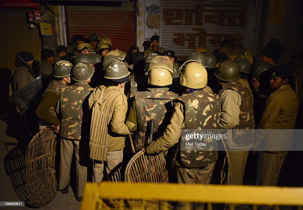 Policemen stand guard after 23-year old Delhi gang rape victim body being taken in an ambulance after arrival at AFS Palam in New Delhi in wee hours on Sunday.