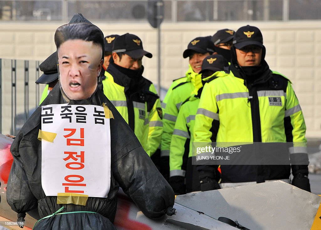 Policemen stand guard as South Korean conservative activists postition an effigy (L) of North Korean leader Kim Jong-Un before setting it alight during a protest denouncing North Korea's rocket launch the day before, in Seoul on December 13, 2012. North Korea's rocket launch is a timely boost for its young leader, securing his year-old grip on power and laying to rest the humiliation of a much-hyped but failed launch eight months ago, analysts say. AFP PHOTO / JUNG YEON-JE
