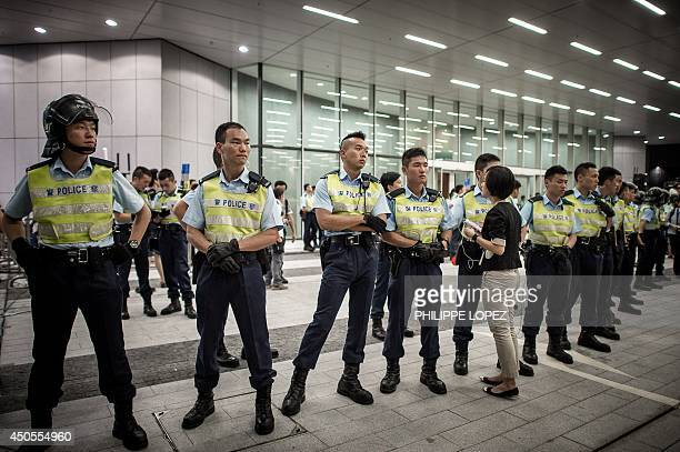 Policemen stand guard at the doors of the Legislative Council after pushing back demonstrators in Hong Kong on June 13 2014 Riot police were deployed...