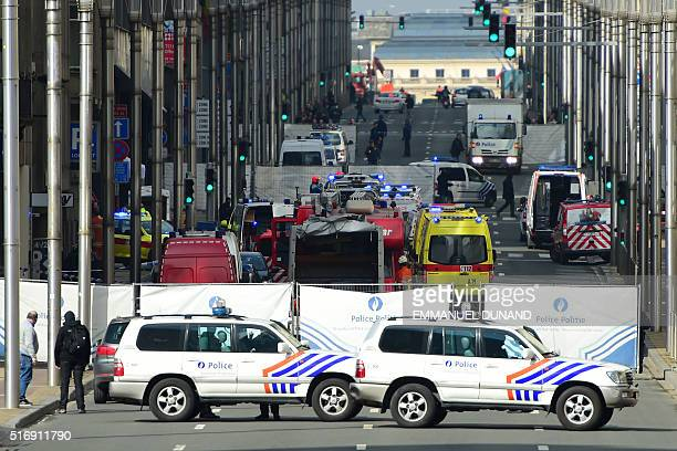 Policemen stand guard at the entrance of a security perimeter set near Maalbeek Maelbeek metro station on March 22 2016 in Brussels after a blast at...