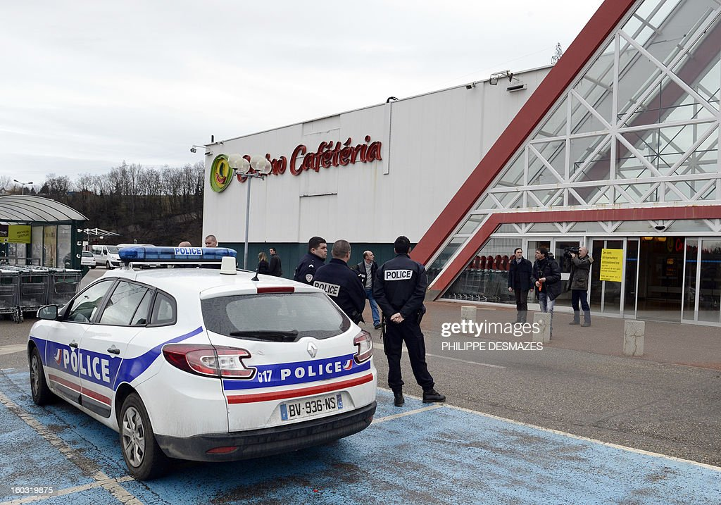 Policemen stand guard in front of a supermaket where a woman had her throat cut by a man who ran away, on January 29, 2013 in La Ricamarie, central France.