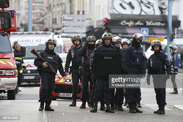 Policemen stand guard in the northern Paris suburb of SaintDenis city center on November 18 as French Police special forces raid an appartment...