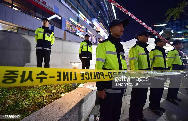 Policemen stand guard near a broken ventilation grate after concert goers fell through it into an underground parking area below in Seongnam City...