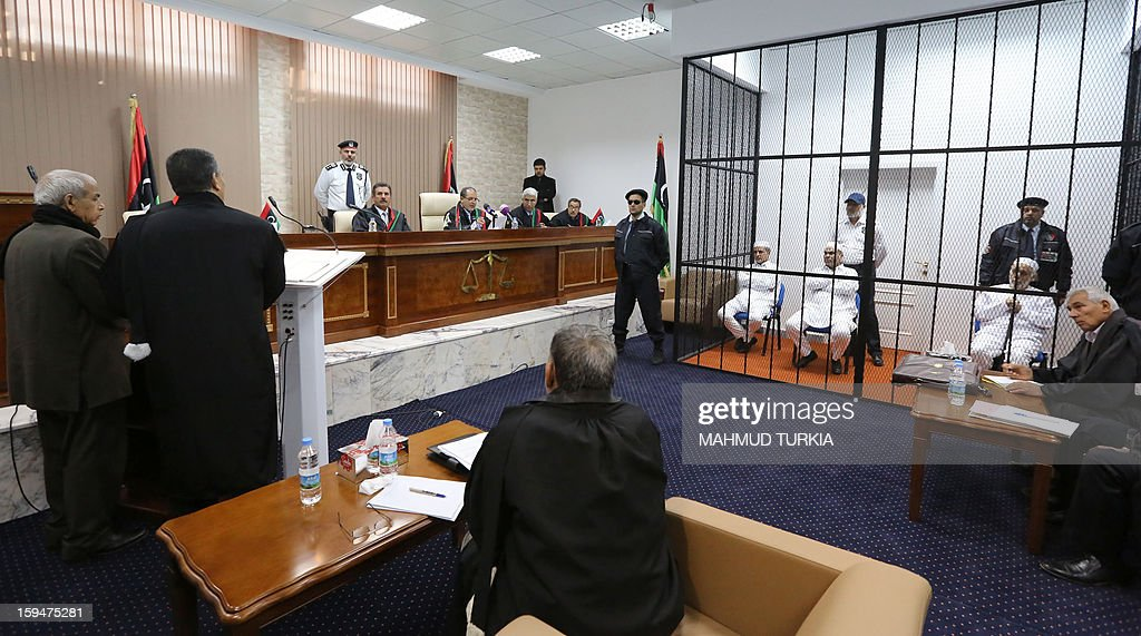 Policemen stand guard next to former Libyan prime minister Baghdadi al-Mahmudi (R), Mabrouk Zhmul (C) and Amer Saleh Tervas (L) from the official African Investment Company, as they sit behind bars in a courtroom in Tripoli as their trials continues in Tripoli, on January 14, 2013. The trial of Mahmudi, late Libyan dictator Moamer Kadhafi's last prime minister, continues in the Libyan capital as he faces charges of 'prejudicial acts against the security of state'.
