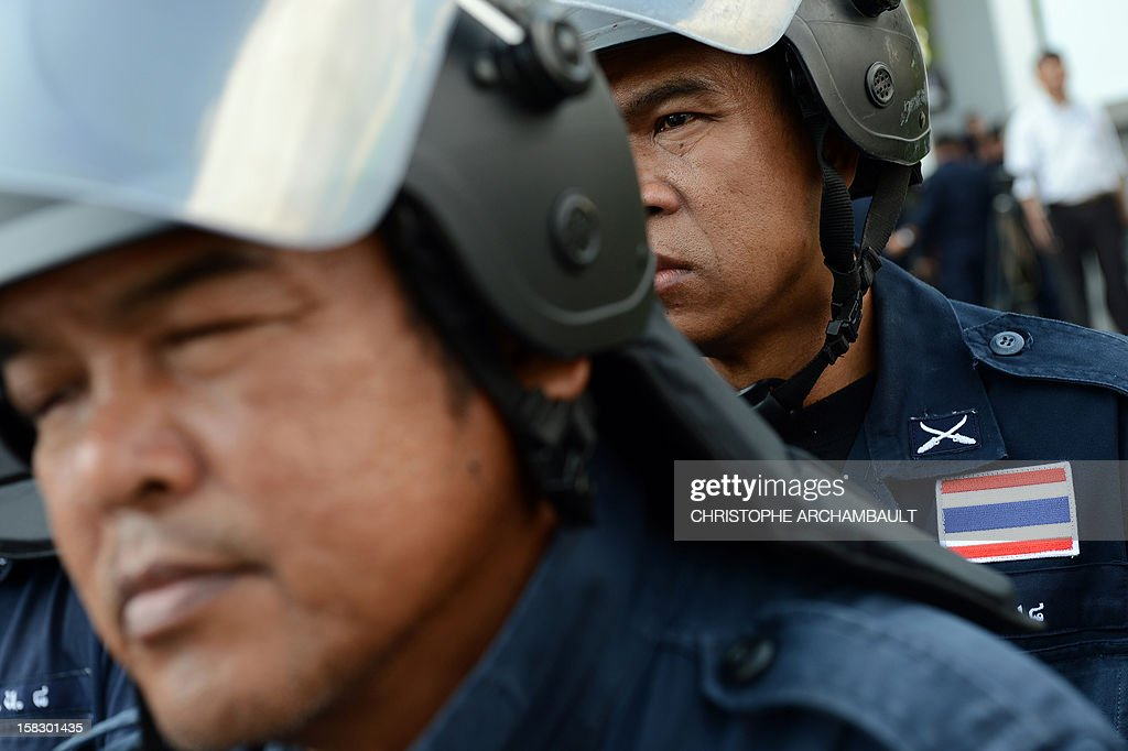 Policemen stand guard outside a justice ministry building where former Thai prime minister Abhisit Vejjajiva arrived to be charged with murder over a civilian's death during a crackdown on anti-government rallies two years ago in Bangkok on December 13, 2012. Abhisit, along with his then-deputy Suthep Thaugsuban, were to be charged at the Department of Special Investigation (DSI), making them the first officials to face a court over Thailand's worst political violence in decades. AFP PHOTO/Christophe ARCHAMBAULT