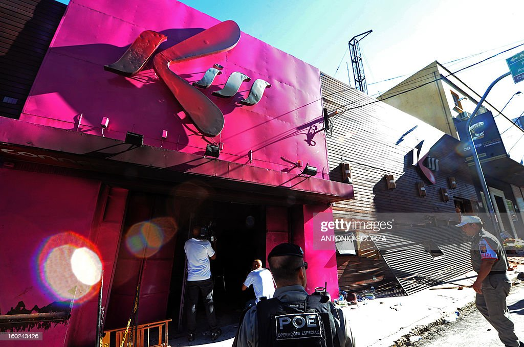 Policemen stand guard outside the Kiss nightclub where a blaze on the eve killed more than 230 people, on January 28, 2013, in Santa Maria, southern Brazil. Brazilian police arrested four suspects --two of the Kiss club's owners, along with a pair of musicians who starred in the ill-fated pyrotechnic show, in the wake of the nightclub fire that forced sports officials to defend preparations for the World Cup and Olympics.. AFP PHOTO ANTONIO SCORZA
