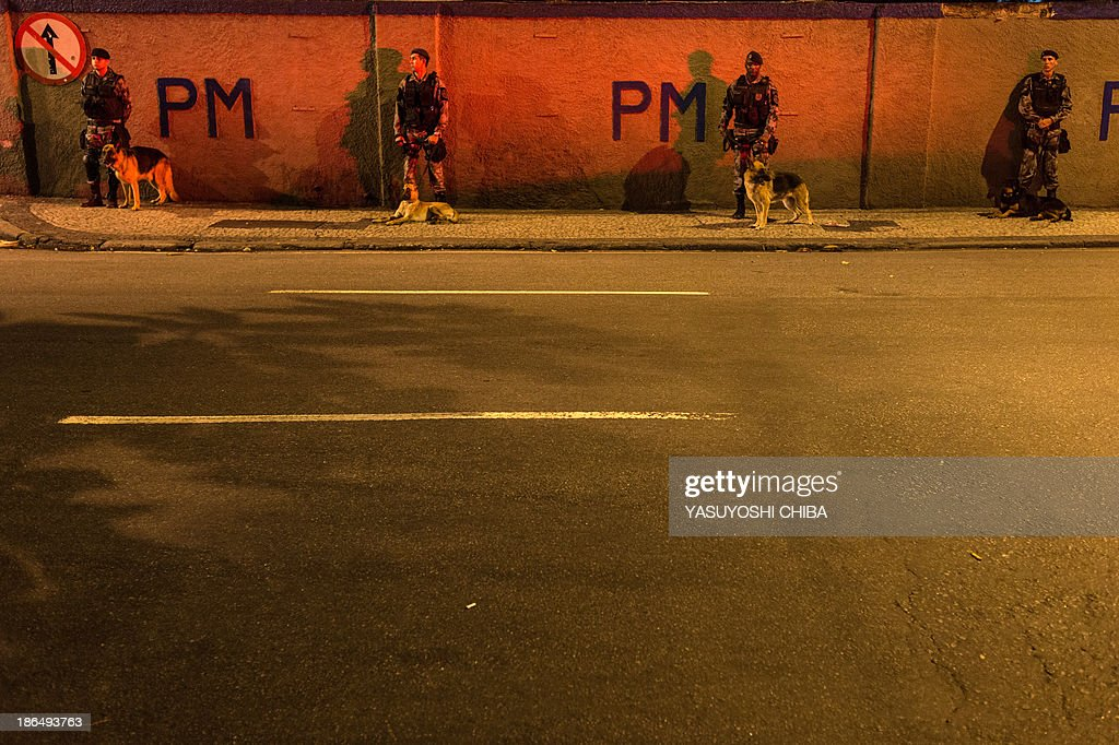 Policemen stand guard with dogs during a silent demonstration against police violence, political corruption and for better public services in Rio de Janeiro, Brazil, on October 31, 2013.