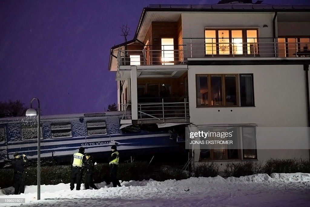Policemen stand in front of a local train that derailed into a residential building in Saltsjoebaden, Sweden, on January 15, 2013. A domestic cleaner stole the train and drove it into the building and was taken to hospital after the crash. AFP PHOTO / SCANPIX SWEDEN/ JONAS EKSTROMER SWEDEN OUT