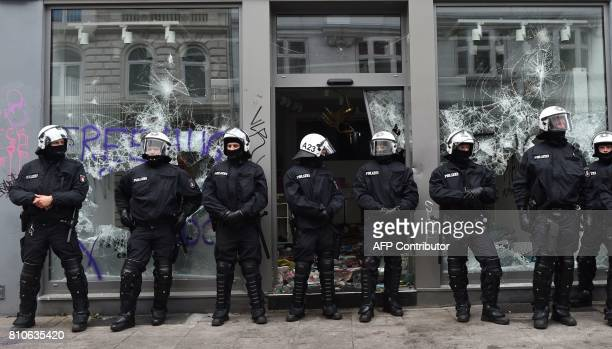 Policemen stand in front of a looted shop after riots in Hamburg's Schanzenviertel district on July 8 2017 in Hamburg northern Germany where leaders...