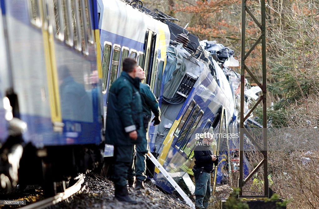 Policemen stand in front of one of the destroyed trains at the site of a train accident near Bad Aibling, southern Germany, on February 9, 2016. Two Meridian commuter trains operated by Transdev collided head-on near Bad Aibling, around 60 kilometres (40 miles) southeast of Munich, killing at least eight people and injuring around 100, police said. The cause of the accident was not immediately clear. / AFP / dpa / Uwe Lein / Germany OUT