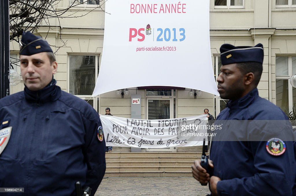 Policemen stand in front of the Socialist party (PS) headquarters on January 3, 2013 in Paris after a protest of three men who chained themselves to the gate of the PS headquarters. The men call for the regularization of immigrants in the French northern city of Lille. Protestors claimed to act in support of Lille's fifty people who have begun a hunger strike since early November. Banner read : 'Should we die for papers? Lille : 63 days of strike' (bottom) and 'PS 2013: Happy New year' (top).