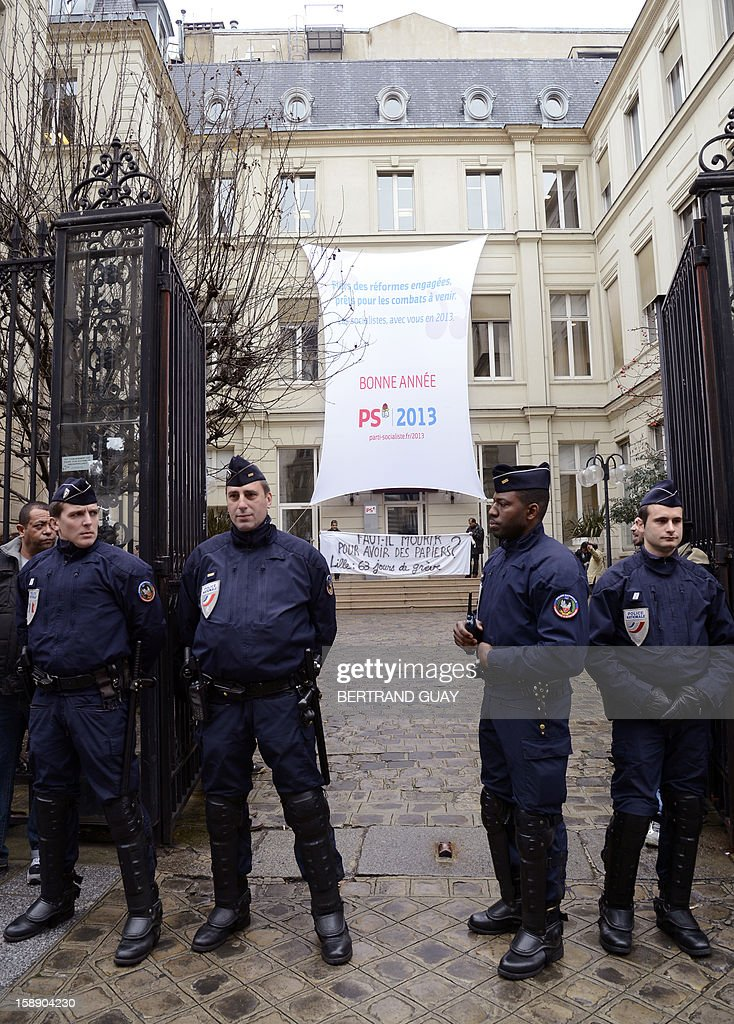 Policemen stand in front of the Socialist party (PS) headquarters on January 3, 2013 in Paris after a protest of three men who chained themselves to the gate of the PS headquarters. The men call for the regularization of immigrants in the French northern city of Lille. Protestors claimed to act in support of Lille's fifty people who have begun a hunger strike since early November. Banner read : 'Should we die for papers? Lille : 63 days of strike' (C) and 'PS 2013: Happy New year' (C-top).