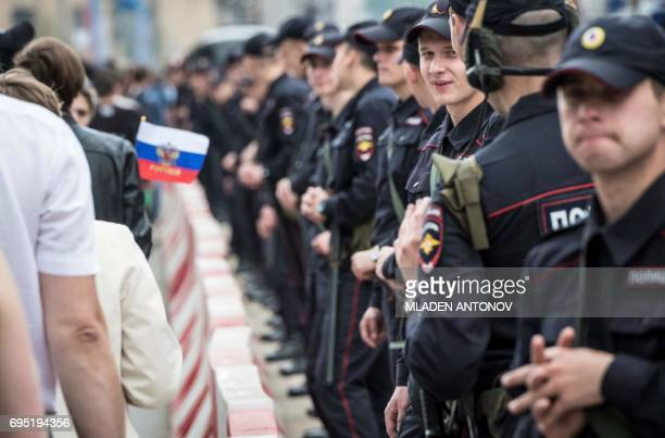 Policemen stand in line at the entrance to Tverskaya street as an unauthorized opposition rally takes place in central Moscow on June 12 2017 Over...