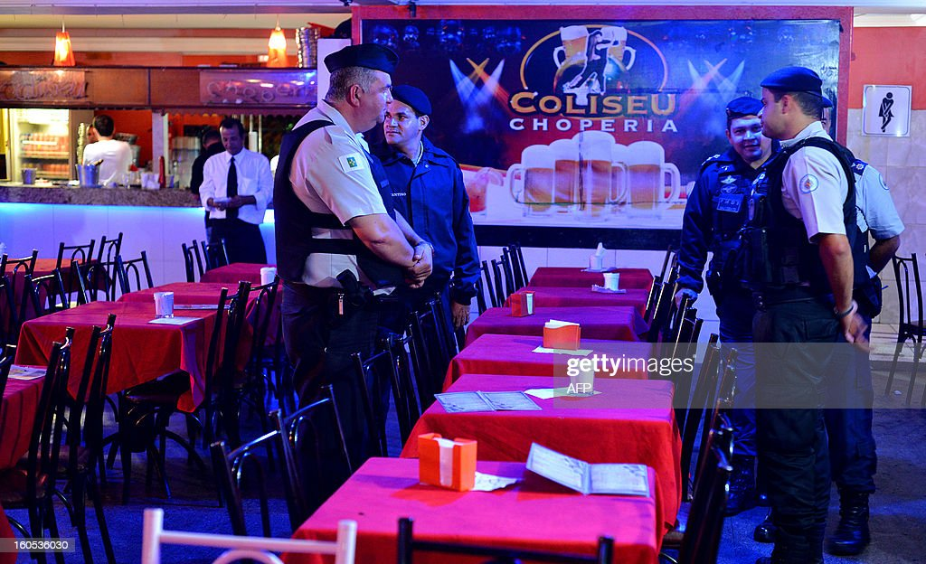 Policemen stand inside a bar that was closed because of an expired license in a suburb of Brasilia, on February 2, 2013. The Brazilian authorities ordered the inspection of many bars and nightclubs all over the country after the blaze in the Kiss Nightclub in Santa Maria, southern Brazil, that left more than 230 people dead. AFP PHOTO/ Pedro LADEIRA STR /pl/pa