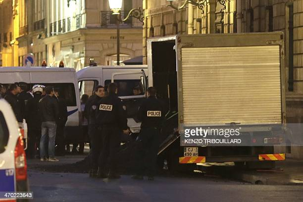 Policemen stand near a lorry containing five tons of coal spilled by Greenpeace activists outside the Elysee Palace in Paris on February 19 a few...
