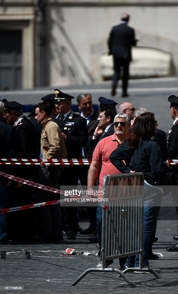 Policemen stand near the area where a Carabiniere police officer was shot by an apparently disturbed man, on April 28, 2013 in Rome, outside the palazzo Chigi, the Italian Prime minister offices, while the country's new ministers were being sworn in. Two policemen were wounded, as well as a passerby, in the shooting. The attacker, named by Italian media as businessman Luigi Preiti, 49, was tackled to the ground by by police as witnesses fled the scene.