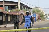 Policemen stand near the La Terrasse restaurant as seen in the backround with the blue curtains in Bamako on March 7 after five people including a...
