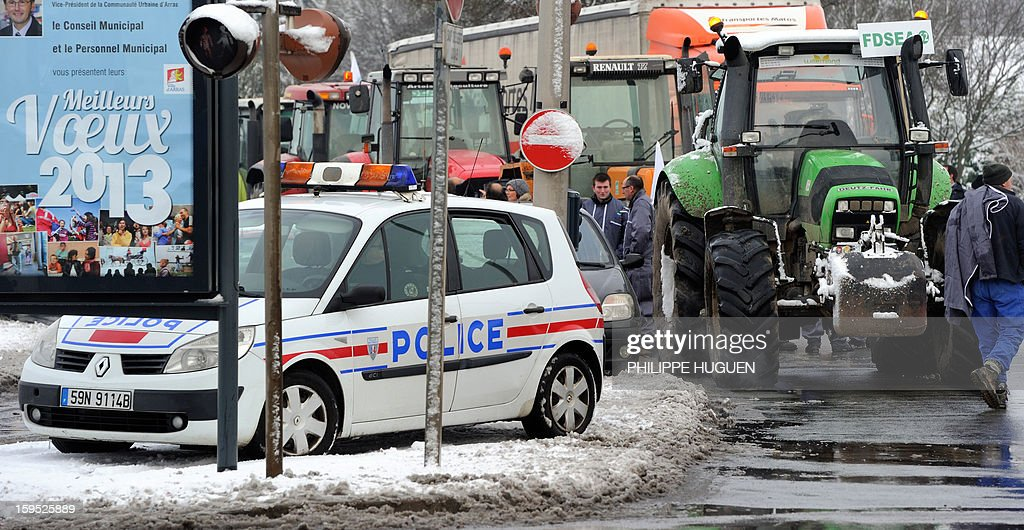 Policemen stand near the partial blockade organized by farmers with some hundred tractors during a demonstration called by farmers local union FDSEA in Arras, northern france, on January 15, 2013. They denounce all kinds of pressure affecting their activities. The municipalty board at left reads : 'Best wishes'. AFP PHOTO PHILIPPE HUGUEN