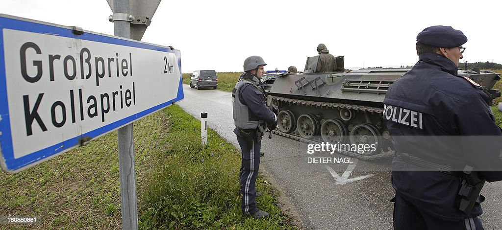 Policemen stand next to an armored vehicle of the Austrian army on September 17, 2013 on a road leading to Grosspriel, Austria, where a poacher has shut himself in a farmhouse with a hostage. Police had attempted to stop the man in his car late on September 16, 2013 near Annaberg, some 100 kilometres (60 miles) west of Vienna, but he shot dead two police officers and an emergency worker and has taken another officer hostage on his run, reports said.